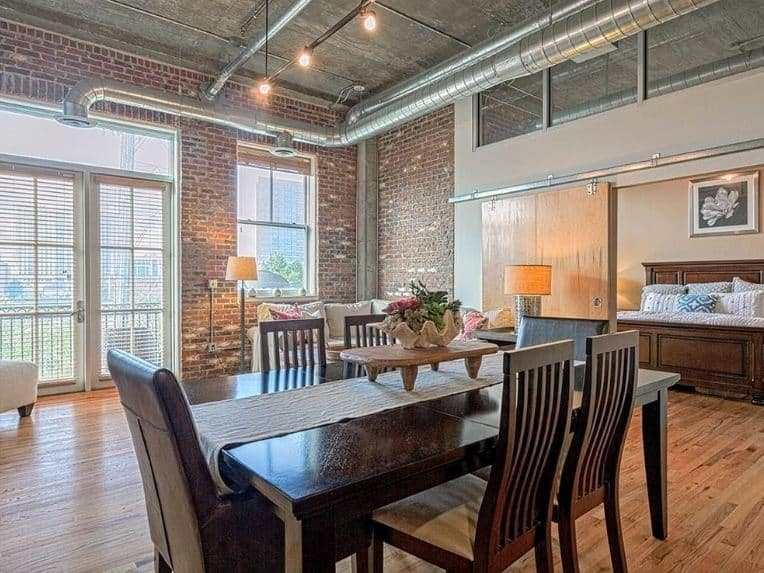 The elegant wooden dining set stands out against the industrial-style elements of this dining area like the red brick walls and the exposed pipes, vents and ducts of the gray high concrete ceiling above.