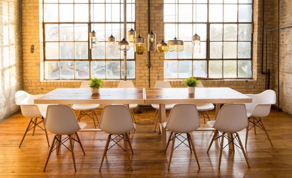 The charming dining room has a relaxing tone to its natural lights that illuminate the hardwood flooring and wooden dining table. This makes the white modern chairs shine brighter and the uniqueness of the pendant lights stand out.