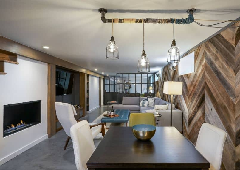 This small dining area beside the living room has the same wooden wall with a herring bone pattern and gray concrete flooring that contrasts the white cushions of the dining chairs of the dark wooden table topped with pendant lights.