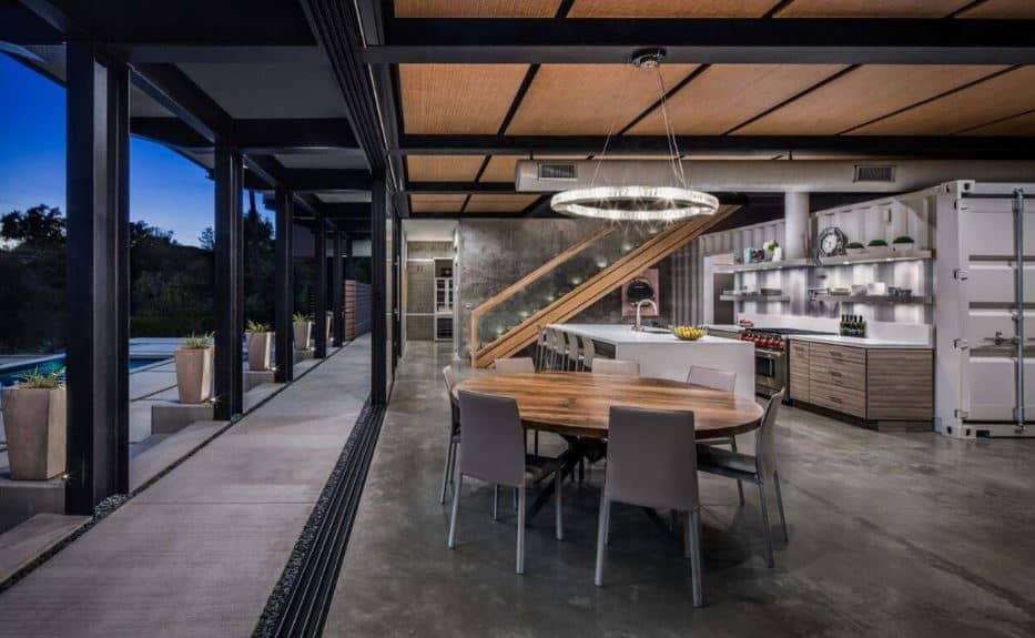 The circular wooden table is paired with light gray modern dining chairs that are matched with the gray industrial flooring topped with a wooden ceiling with exposed metal beams and a background of a repurposed shipping container at the kitchen.