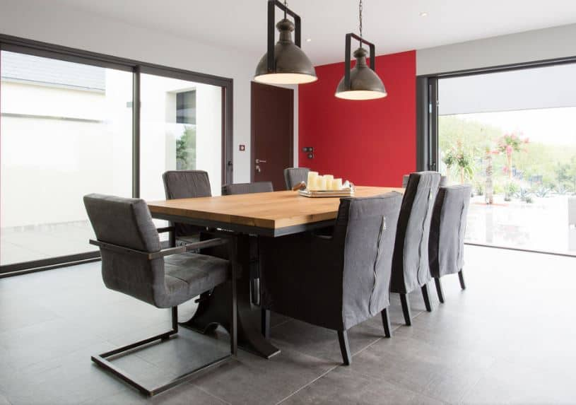 The dining table has dark metallic legs that match the dark gray velvet cushions of the chairs. The table has a thick slab of wood on top that stands out against the gray industrial-style flooring and the dark pendant lights above.