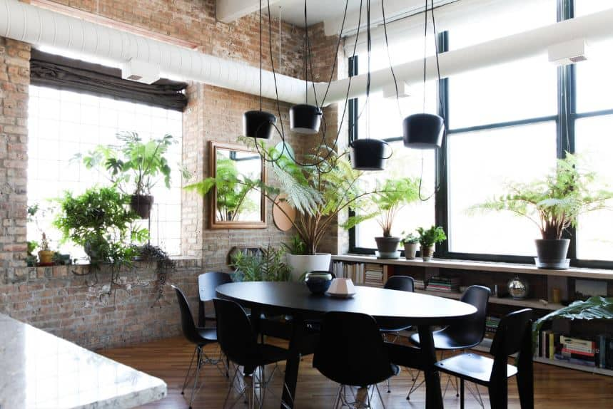 The oblong black dining table is paired with equally dark modern dining chairs. This setup is complemented by the dark hardwood flooring and the red brick walls brightened by large windows and white air ducts.