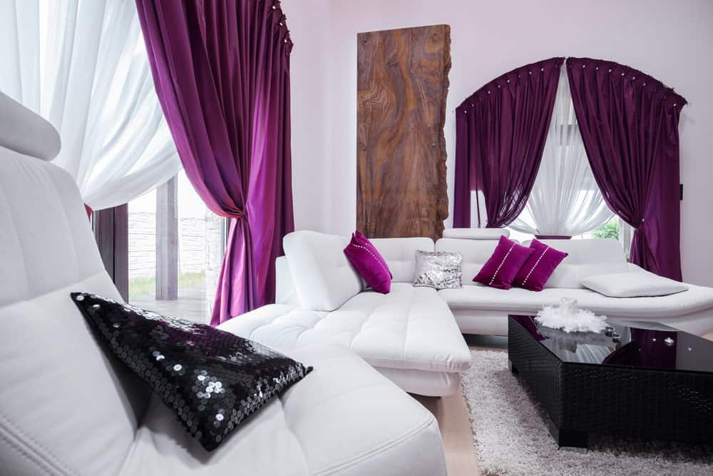 This living room features sleek seats and white walls accented with purple pillows and classy draperies. It includes a black coffee table that sits on a gray shaggy rug over the light hardwood flooring.