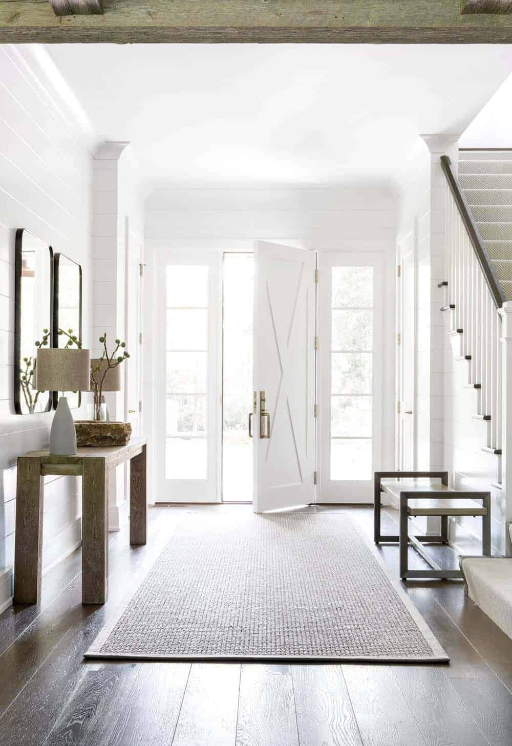 The white wooden door has a distinct Farmhouse-style design to it complemented by the white walls that has a shiplap plank finish. These are brightened by the natural lights coming in from the side lighting. There is also a wooden on the side opposite to the wooden console table.