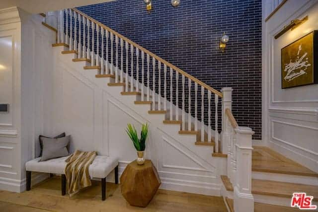 This foyer has a lovely view of the wooden staircase that has white railings and wooden steps contrasted by the black wall with a brick wall finish. Below the stairs is a comfortable waiting area with a cushioned bench that blends with the white wooden walls.