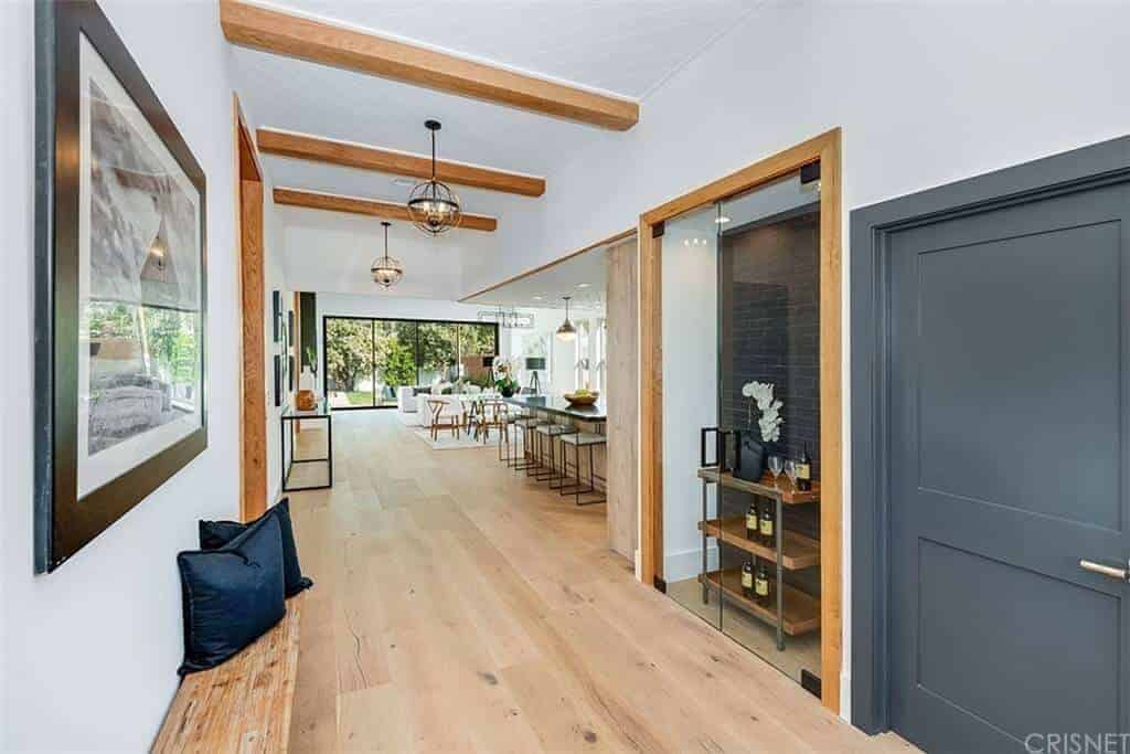 This foyer has a light hardwood flooring that complements the the wooden molding of the walls and the exposed wooden beams of the ceiling. It also matches the small wooden built-in bench on the left side under a wall-mounted framed artwork.