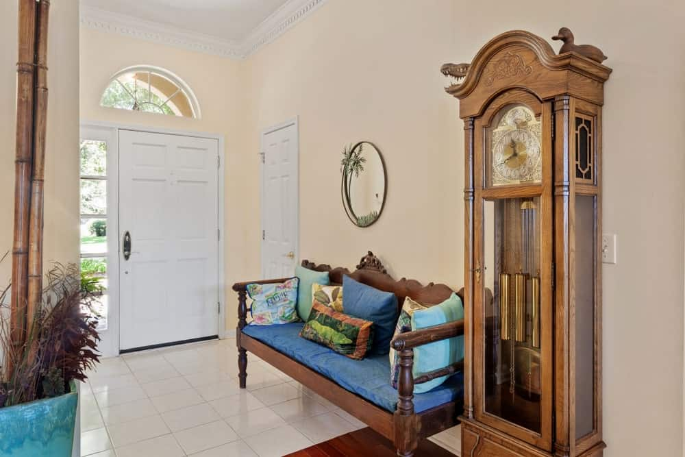 Upon entry of the white wooden main door, the guests are welcomed by a wooden bench with a blue cushions on it. Beside this bench is a grandfather clock with a wooden carving of a duck above it. These complement the beige walls and white floor tiles.