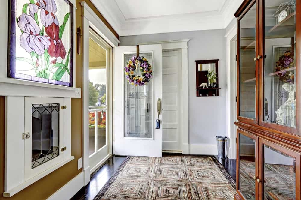 This amazing foyer has a fireplace and a stained glass panel window above it that seem to glow with the natural lights. This fireplace has a white frame that stands out against the brown walls and matches with the white wooden main door that has a second layer screen door.