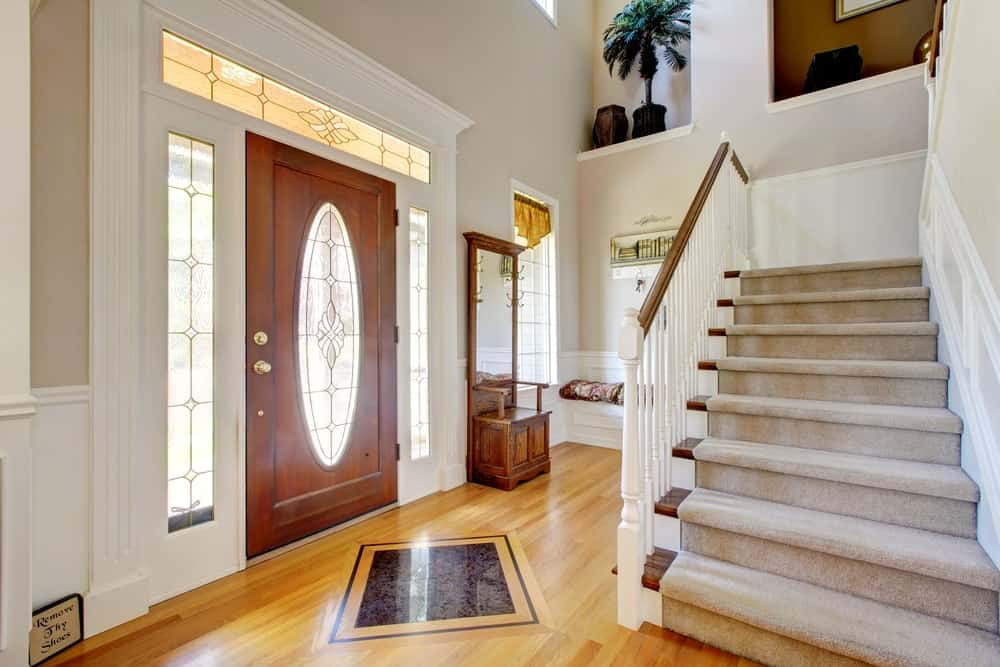 The wooden main door has an elliptical frosted glass panel in the middle that matches with the design of the glass panels of the side lights and the transom window. These are all framed with a white molding that stands out against the redwood flooring.