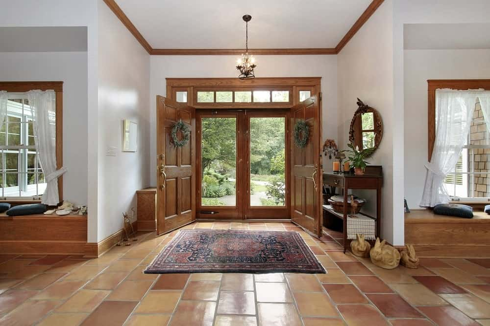 The terracotta flooring is a nice earthy complement to the white walls and white ceiling that hangs a small pendant light over the entry. These are also complemented by the wooden elements of the doors, molding and the wooden console table.