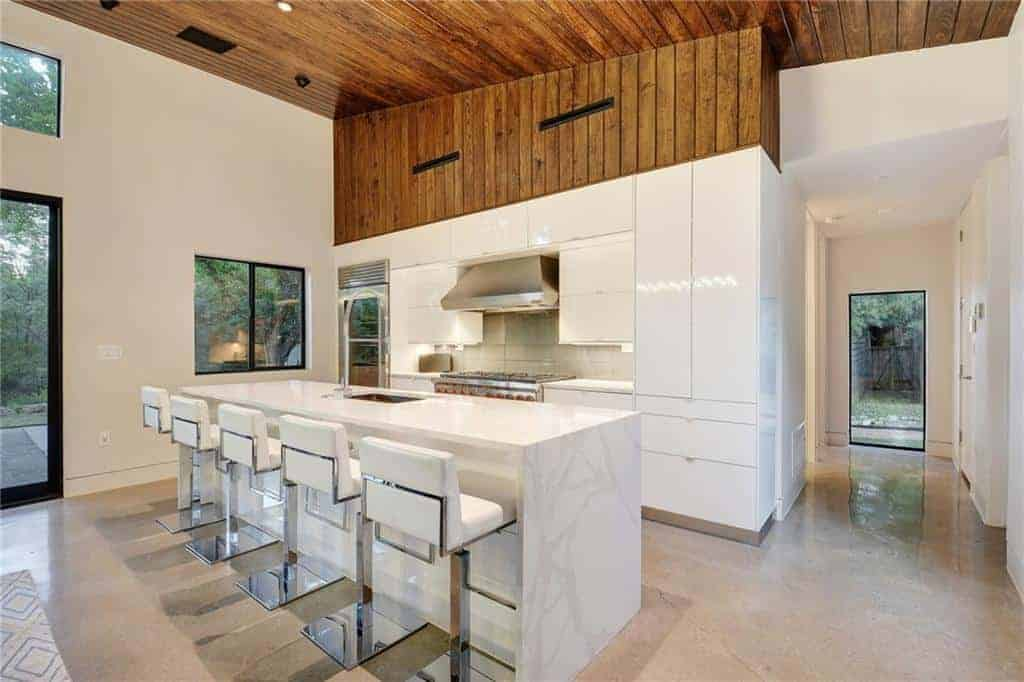 The waterfall white marble kitchen island matches with the pure white cabinets of the kitchen peninsula that houses the stainless steel appliances. This is topped with a wooden ceiling that extends to the upper wall.