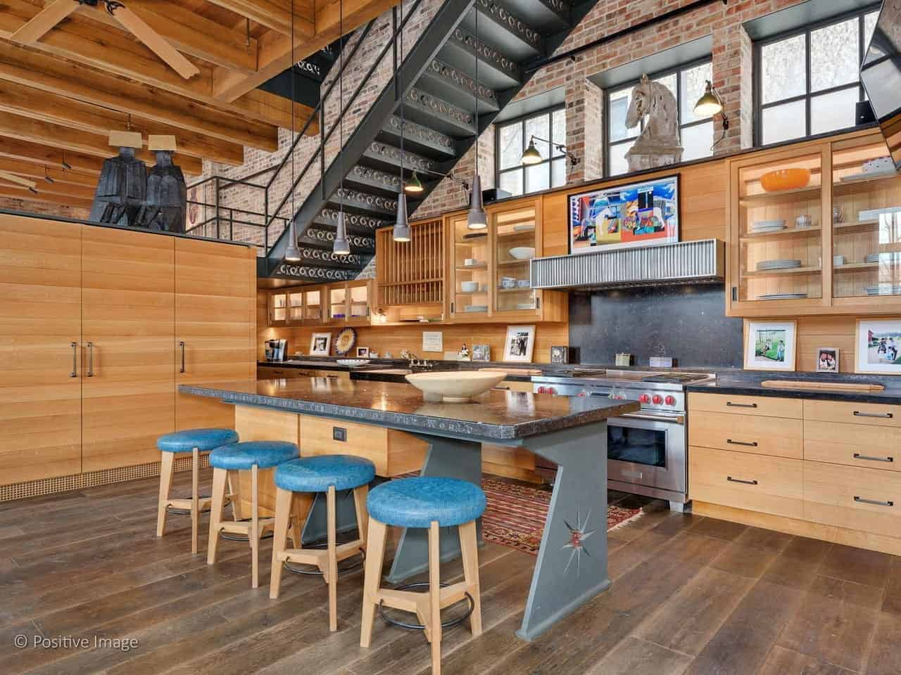 This industrial-style kitchen has a high wooden ceiling with exposed wooden beams. This matches with the wooden structures of the kitchen cabinets and drawers customized to fit under the metal stairs with a brick wall.