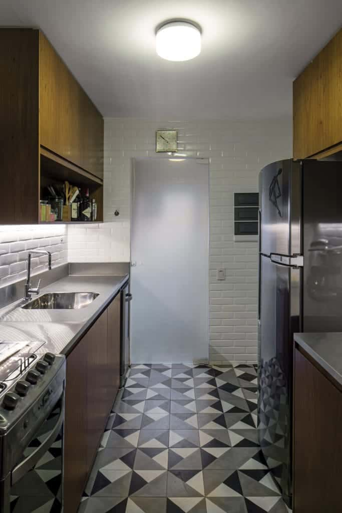 This small kitchen has white wall tiles that are arranged in a brick wall pattern. This is a nice complement to the complex patterned flooring tiles made of white, black and gray triangles. This matches the appliances and the countertops.