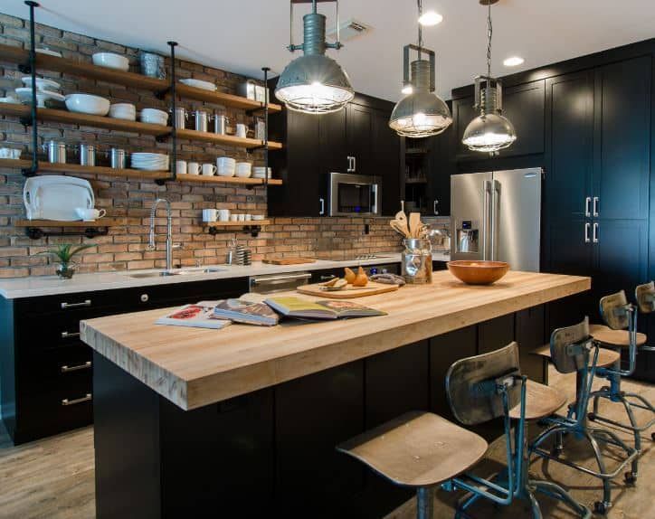 The industrial-style pendant lights are a great complement for the butcher block countertop of the black kitchen island matching with the peninsula that houses the stainless steel appliances complemented by the red brick walls.