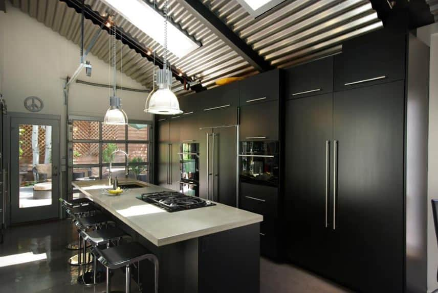 The shed ceiling is made of stainless tin roofing sheets that are held together by exposed dark beams. This ceiling also has sky lights that cast natural lights down onto the modern kitchen that is mostly black and gray.