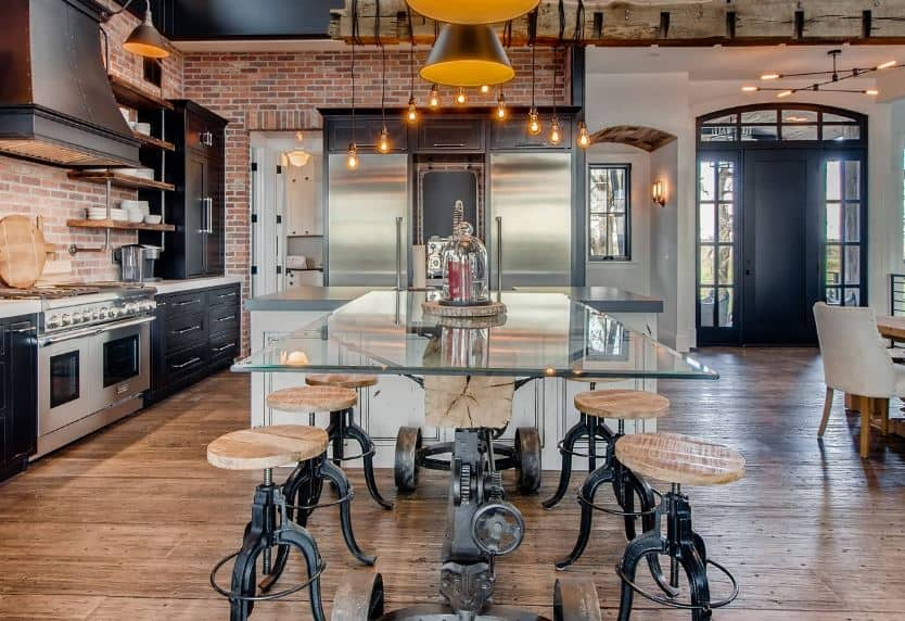 The red brick walls makes the black cabinets of the peninsula stand out along with the stainless steel appliances that it houses. This is complemented by a hardwood flooring and a gray concrete ceiling with exposed vents and wirings.