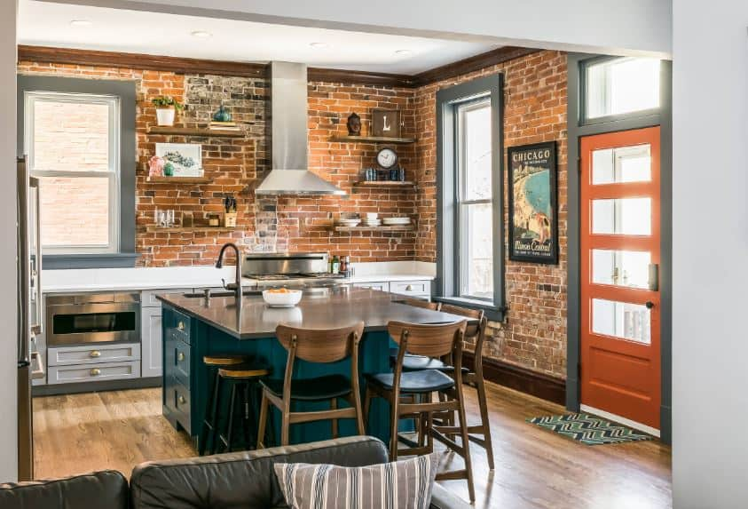 The green cabinets and drawers of the kitchen island stands out against the red brick walls of the kitchen peninsula that has gray shaker cabinets and drawers housing the stainless steel appliances and its vent hood above.
