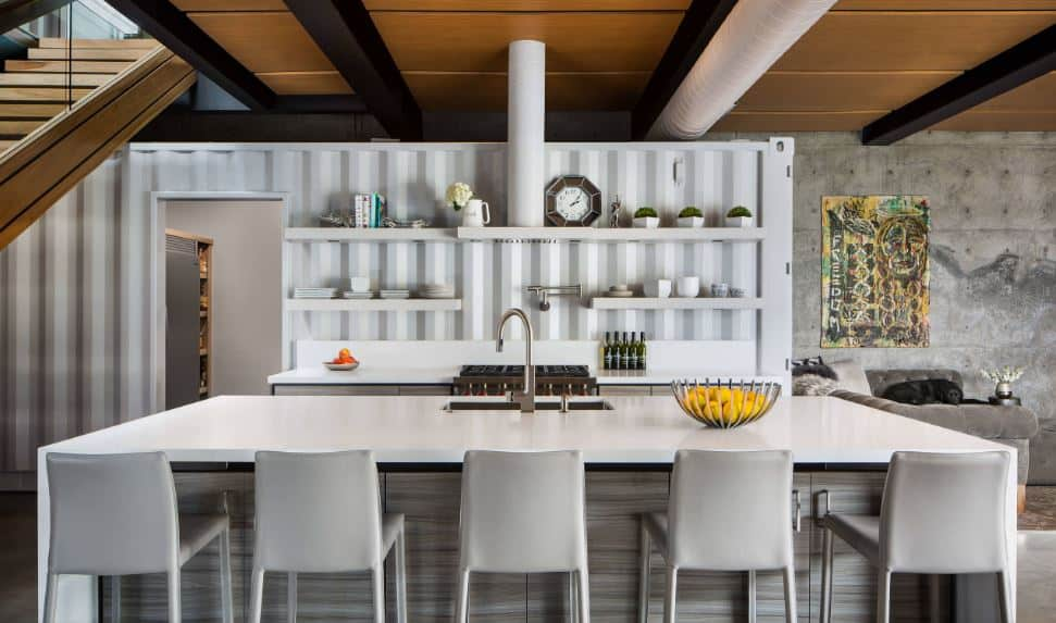 The white countertop of the peninsula goes well with the white wall that looks like a part of a shipping container. This is paired with white shelved and a white vent hood and air duct on the wooden ceiling with exposed black beams.