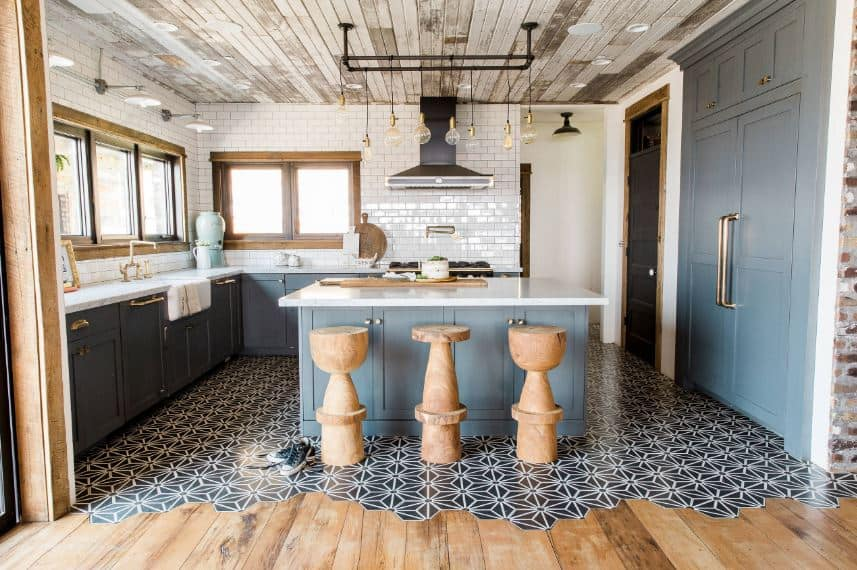 The distressed wooden ceiling is paired with a complex flooring filled with patterns. These are a nice background for the light gray shaker cabinets and drawers of the kitchen island and L-shaped peninsula with white countertops.