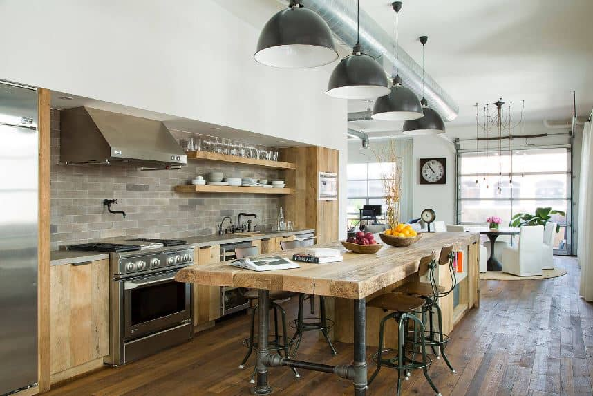 The large wooden kitchen island has a thick butcher block countertop that is supported by legs made of water pipes. This goes well with the exposed vent and duct of the white ceiling as well as the gray backsplash of the wooden peninsula.