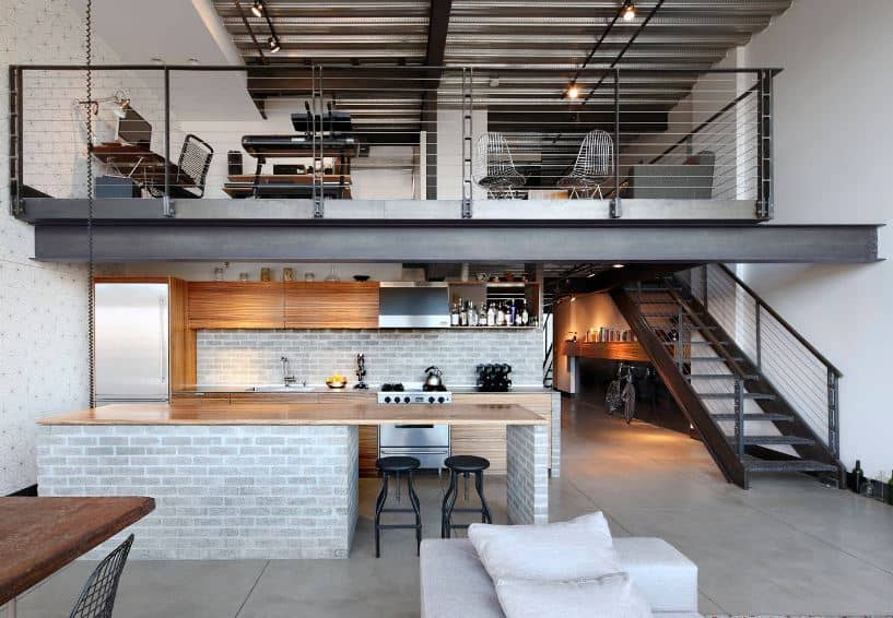 This charming kitchen is framed on two sides by the black metal beam above that supports the loft and the black metal beam of the stairs on the right. This gives a nice contrast to the light hue of the brick walls that match the kitchen island.