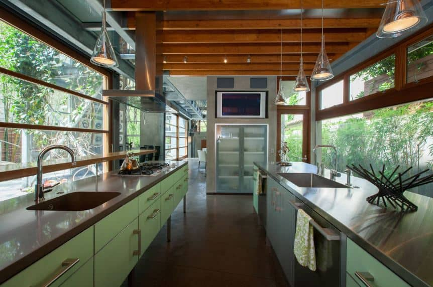 This narrow kitchen is flanked on both sides with glass walls that offer a nice green landscape scenery outside. This matches with the green modern cabinets of the two peninsulas with gray countertops that goes well with the wooden ceiling and its exposed wooden beams.
