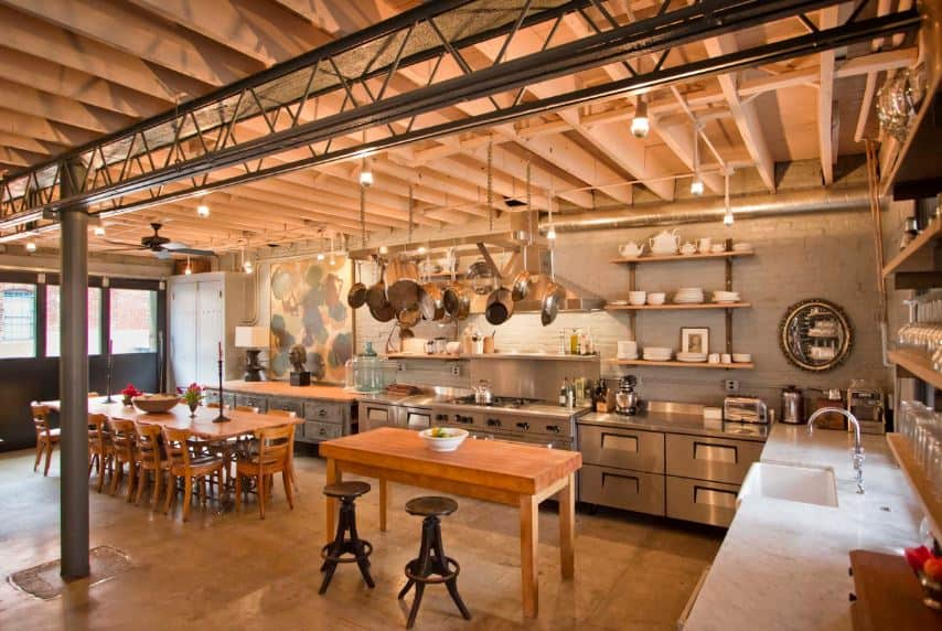 This industrial-style kitchen shares its wide wooden ceiling with the dining area beside it. This wooden ceiling that has exposed wooden beams are supported by a metal column connected to metal trusses above that goes well with the metal peninsula.