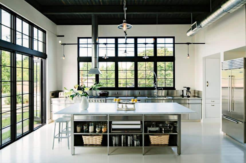 The stainless steel cabinets and shelves of the kitchen island and peninsula matches with the stainless steel appliances as well as with the exposed vents and ducts of the high ceiling that is painted black to match the frames of the glass doors and windows.