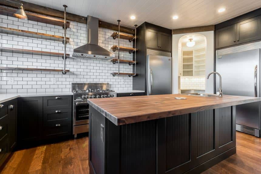 The black shaker cabinets and drawers of the kitchen island and L-shaped peninsula are complemented by the hardwood flooring matching with the countertop of the island. These are contrasted by the white backsplash that supports shelves with pipes as frames.