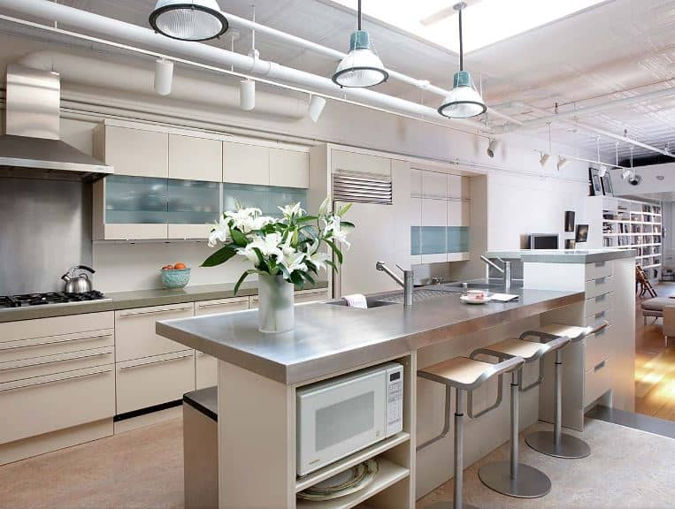 The brilliant white ceiling of this kitchen has exposed white pipes and tubes for the wiring of the spot lights and pendant lights hanging over the kitchen island that has a second level countertop to serve as a bar paired with modern stools.