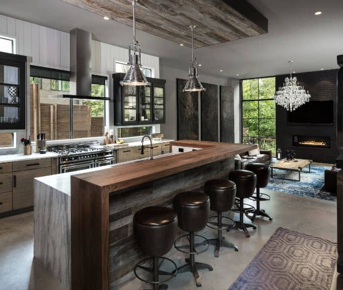 Those beautiful stainless steel pendant light hanging over the kitchen island matches with the stainless steel appliances of the cooking area embedded in the kitchen peninsula that has wooden drawers and cabinets.
