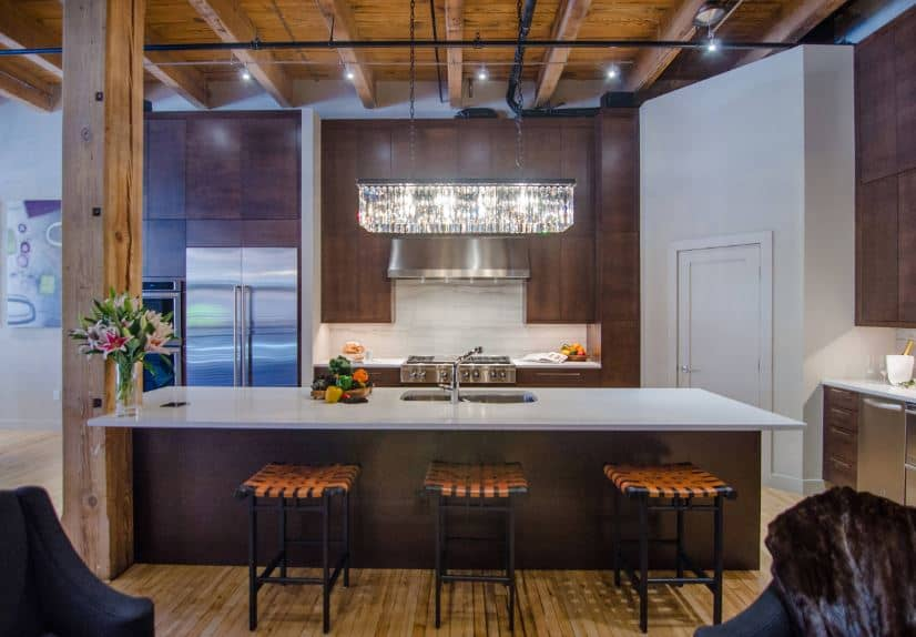 There is a large wooden column that connects the hardwood flooring and the wooden ceiling that has exposed wooden beams of the same hue as the flooring. These are a nice framing for the dark brown kitchen island and peninsula.
