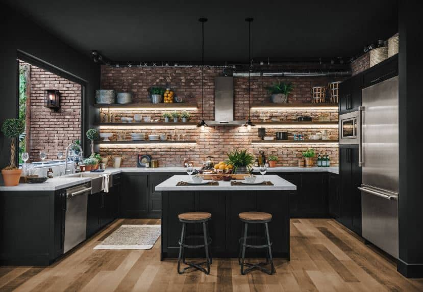 This kitchen is dominated by the black hues of the shaker cabinets and drawers of the kitchen island and U-shaped peninsula as well as the black ceiling. This is complemented by the red brick walls and the hardwood flooring.