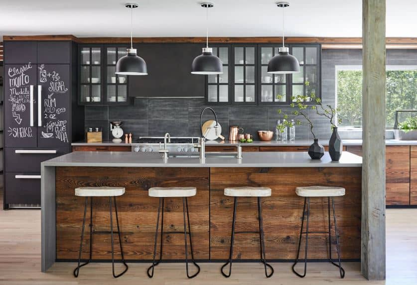 The gray waterfall countertop of the wooden kitchen island blends with the concrete column beside it. These are complemented by a white ceiling with black pendant lights hanging over the kitchen island matching with the black walls.
