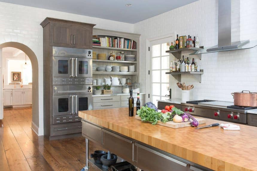 The distressed hardwood flooring of this kitchen is paired with industrial-style cabinets and drawers of the island and peninsula that is made of stainless steel. This goes well with the stainless steel appliances as well as the vent of the cooking area.