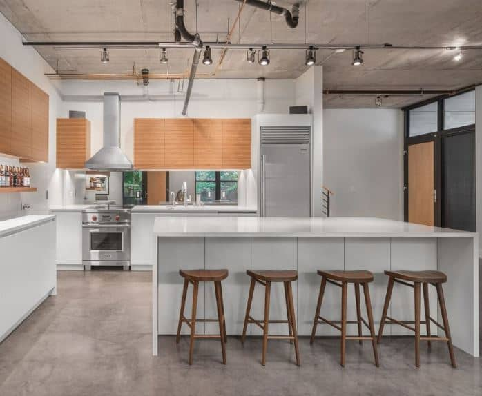 The gray concrete flooring of this industrial-style kitchen matches well with the gray concrete ceiling with exposed pipes and tubes supporting modern spot lights. This serves as a nice framing for the white modern kitchen island and peninsula.