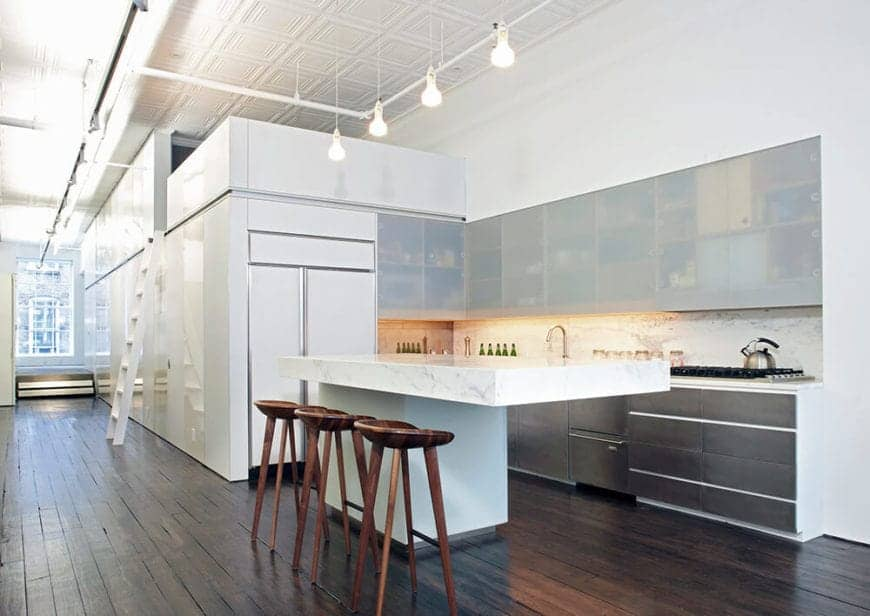 The simple and modern elements of the kitchen are given an industrial-style background with a distressed hardwood flooring, a high white ceiling with exposed pipes and pendant lights hanging over the thick white marble countertop of the kitchen island.