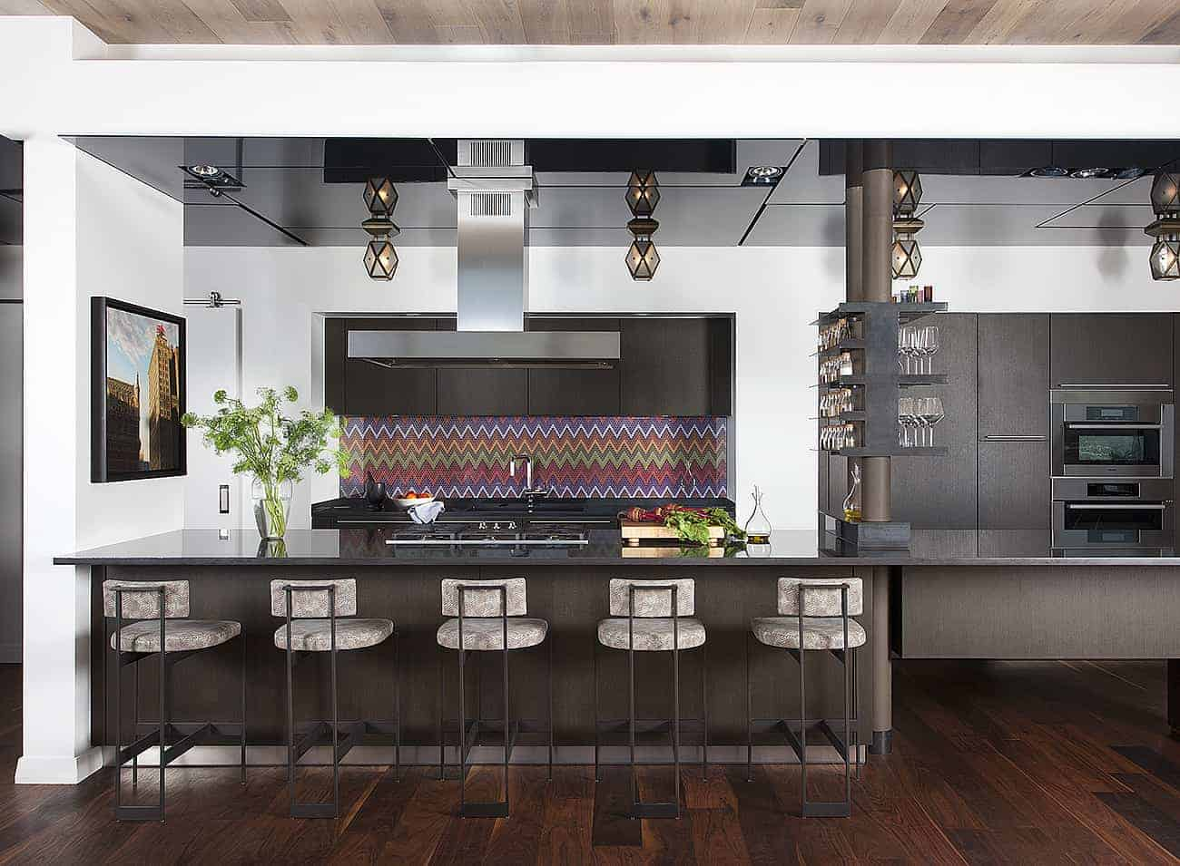The black and white theme of this industrial-style kitchen is complemented by the hardwood flooring and provided with a dash of color from the backsplash that has a quirky pattern that softens up the sleek elements.