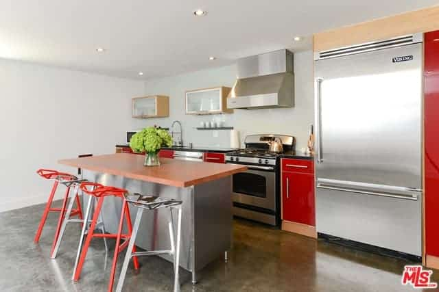 The sleek red elements of this industrial-style kitchen stands out against the stainless steel appliances and kitchen island that matches with the gray concrete flooring brightened by the white walls and ceiling.