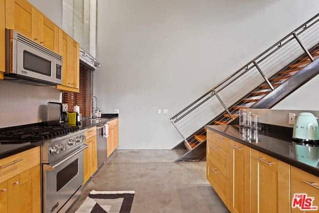 This kitchen has an industrial-style gray concrete floor that complements the stainless steel appliances embedded into the wooden kitchen peninsula that has a background of the metal staircase on the far wall.