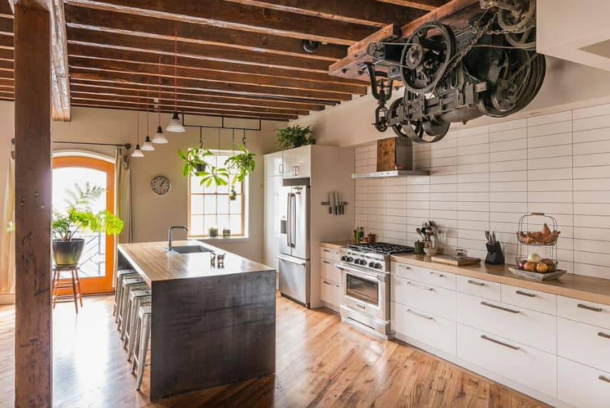This kitchen has a hardwood flooring that matches with the wooden column supporting the wooden ceiling with exposed wooden beams. This ceiling is adorned with an old engine with gears and cogs that bring this kitchen a unique look.