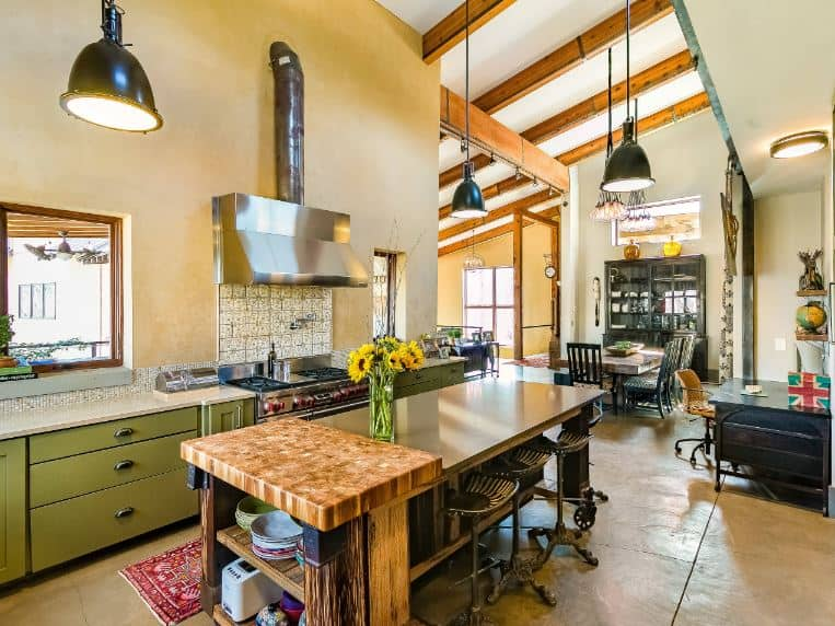 The textured beige flooring of this charming and homey industrial-style kitchen matches with the walls of the peninsula that has green wooden drawers and cabinets flanking the stainless steel stove-top oven topped with a matching vent embedded into the wall.