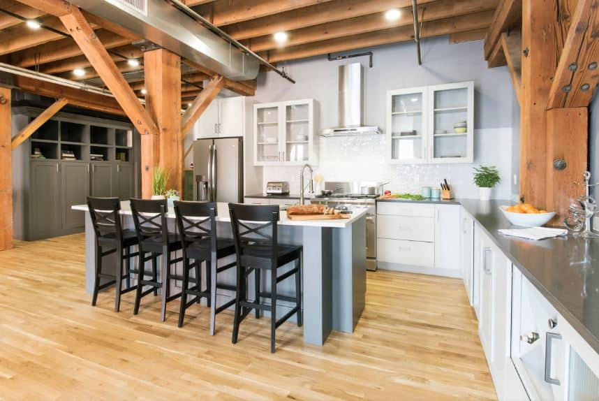 The wooden ceiling has exposed wooden beams that are supported by large wooden columns of the same hue that complements the hardwood flooring. This is contrasted by the black wooden stools paired with the light gray kitchen island.