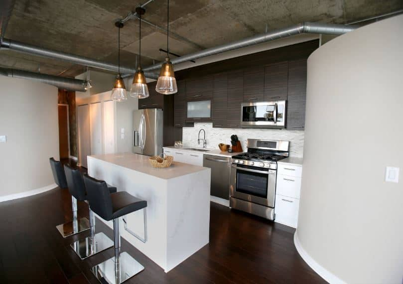 The dark hardwood flooring contrasts the white walls and the white kitchen island that matches the white peninsula. Above this peninsula are dark cabinets that go well with the concrete gray ceiling with exposed vents and ducts.