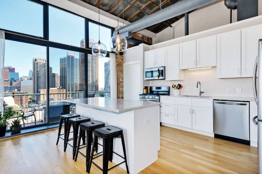 This bright kitchen has a high arched ceiling augmented by a large glass wall that offers a nice urban jungle scenery that brings in natural lights to the white kitchen island and peninsula that houses the stainless steel appliances.