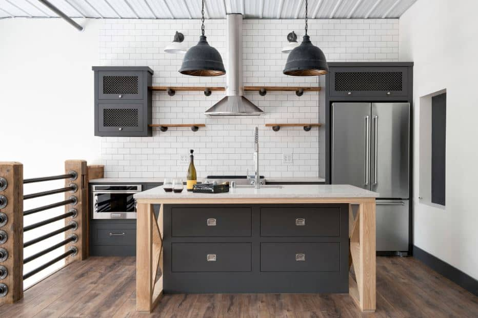 This is a second floor kitchen right beside the railings that have low wooden posts supporting metal rods. This pairs well with the dark gray kitchen cabinets of the island and peninsula with a white brick wall and white metal ceiling.