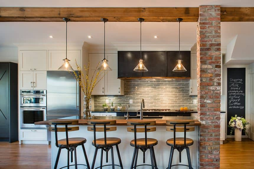 This industrial-style kitchen has a traditional-style twist to its white shaker cabinets and drawers of the kitchen island and peninsula. These are complemented by brick walls and pillars and an exposed wooden beam that supports pendant lights.