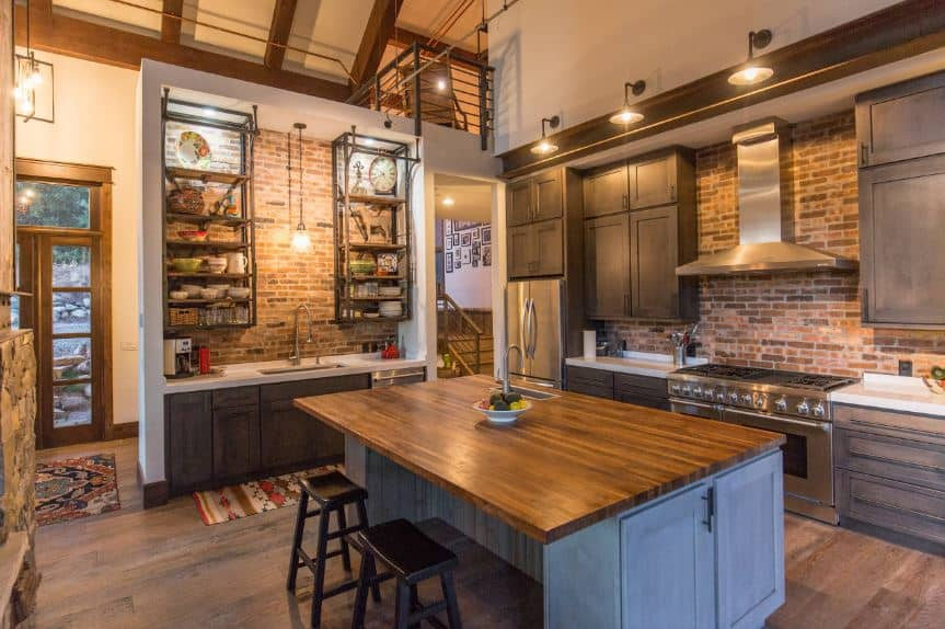 This industrial-style kitchen has a distinct charm to its red brick wall backsplash that complements the dark gray cabinets of the kitchen peninsulas that has matching dark gray floating cabinets and shelves as well as an exposed metal beam above the cooking area.