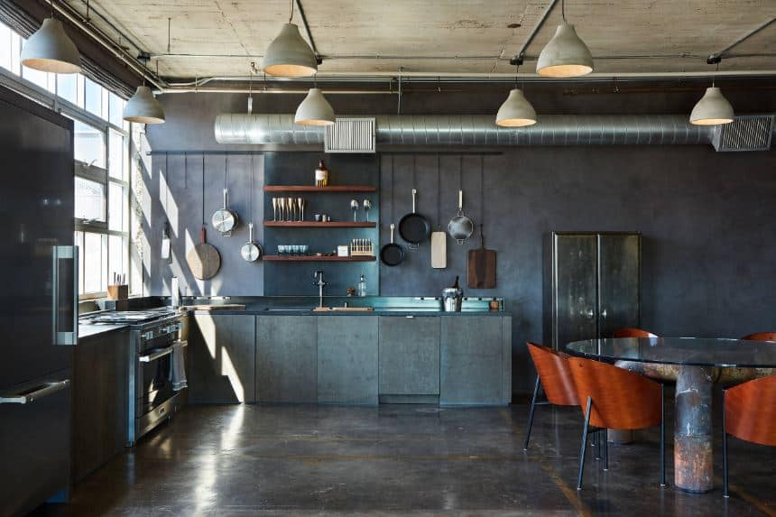This industrial-style kitchen has a concrete gray ceiling with exposed pipes and vents that goes well with the gray walls and gray kitchen peninsula with dark gray countertops that match the stainless steel appliances.