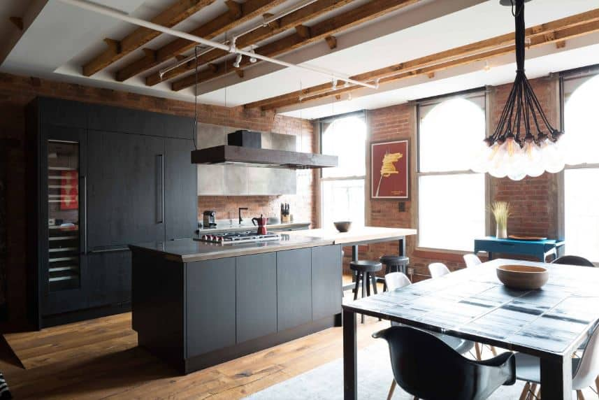 This beautiful industrial-style kitchen has pitch black cabinets on its kitchen island and peninsula that goes well with the red brick walls and hardwood flooring. These are all illuminated by the two windows that bring in an abundance of natural lights.
